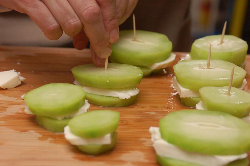 Cortar rebanadas de queso de medio centímetro de espesor y colocar en medio de dos rebanadas de chayote. Unir con un palillo de madera.