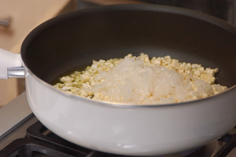 Calentar aceite en una olla honda y agregar los granos de elote junto con la cebolla picada y cocer durante 5 minutos.