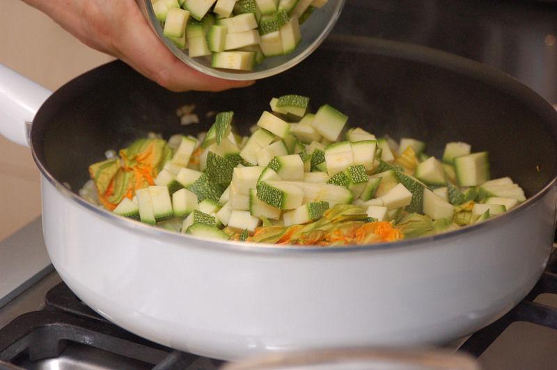 Añadir las flores de calabaza y las calabacitas picadas. Cocer meneando frecuentemente durante 5 minutos más.