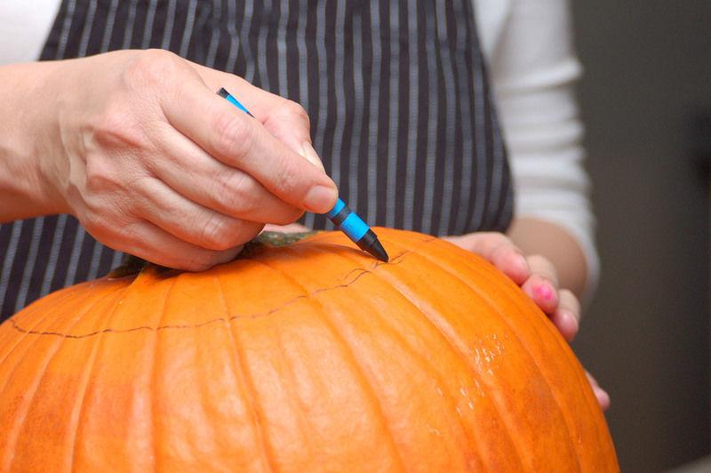 Para hacer la calabaza de Halloween, enjuagar bien el exterior de la calabaza con agua tibia, no utilizar jabón. Secarla y dibujar con un crayón negro un círculo que se separe 8 centímetros del tallo de la calabaza.