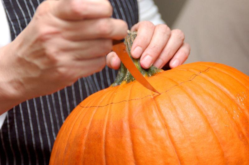Cortar el círculo utilizando un cuchillo para calabaza introduciéndolo a un ángulo de 45°. Levantar el tallo y retirar las semillas de la de la calabaza con una cuchara. Envolver la parte cortada del tallo con papel plástico auto adherible y reservar.