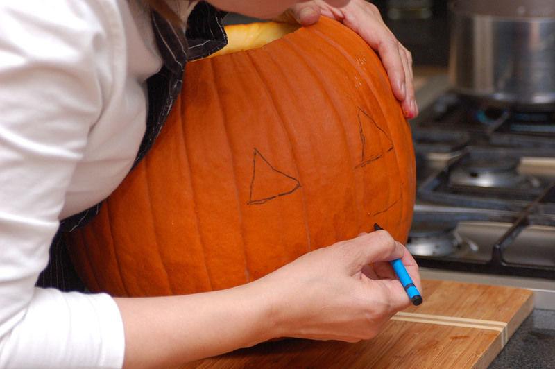 Retirar las semillas de adentro de la calabaza con una cuchara, estas se pueden reservar para hacer pepitas de calabaza. Dibujar los ojos y la boca con el crayón.