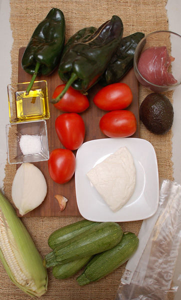 250 gramos de lomo de puerco 6 tazas de agua 4 piezas de calabacita 1 diente de ajo aceite de oliva al gusto sal de mar al gusto 1 pieza de bolsa de plástico 100 gramos de queso fresco 1 pieza de aguacate 1 pieza de elote 1/4 pieza de cebolla blanca 5 piezas de jitomate guaje 4 piezas de chile poblano