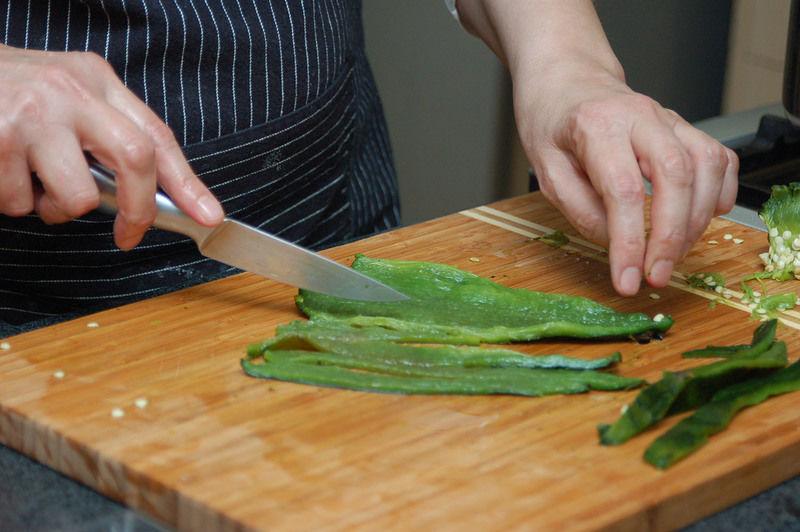 Hacer un corte por un lado de cada chile con un cuchillo para retirar las semillas y las venas. Cortar en rajas y reservar.