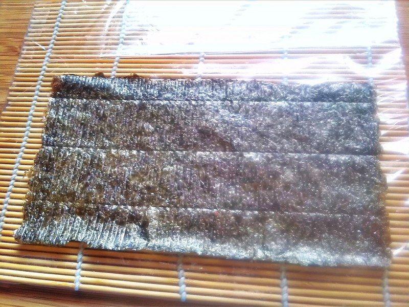 Para el rollo California, coloca un plástico con cinta adhesiva al reverso al tapete de bambú, pon media alga nori encima (también puede ser completa, pero es otro procedimiento), ASEGÚRATE QUE EL LADO MATE O MÁS RUGOSO ESTÉ POR ENCIMA, y el lado brilloso o más liso esté por debajo.