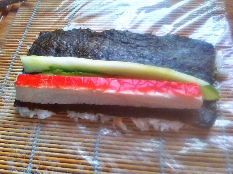 En la orilla del sushi coloca gajos de aguacate, un bastón de pepino y un surimi cortado a la mitad por lo largo, asegúrate de que a todo lo largo, el sushi tenga estos ingredientes, si es necesario coloca un pedazo más de surimi u otro ingrediente para completar, de lo contrario cuando cortes el makizushi, habrá partes que solo tengan arroz.