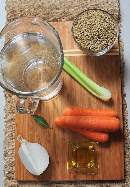 1 pieza de hoja de laurel 3 dientes de ajo 2 litros de agua 4 cucharadas de aceite de oliva pimienta negra molida al gusto sal al gusto 2 varas de apio 1/4 pieza de cebolla blanca 3 piezas de zanahoria 500 gramos de lentejas