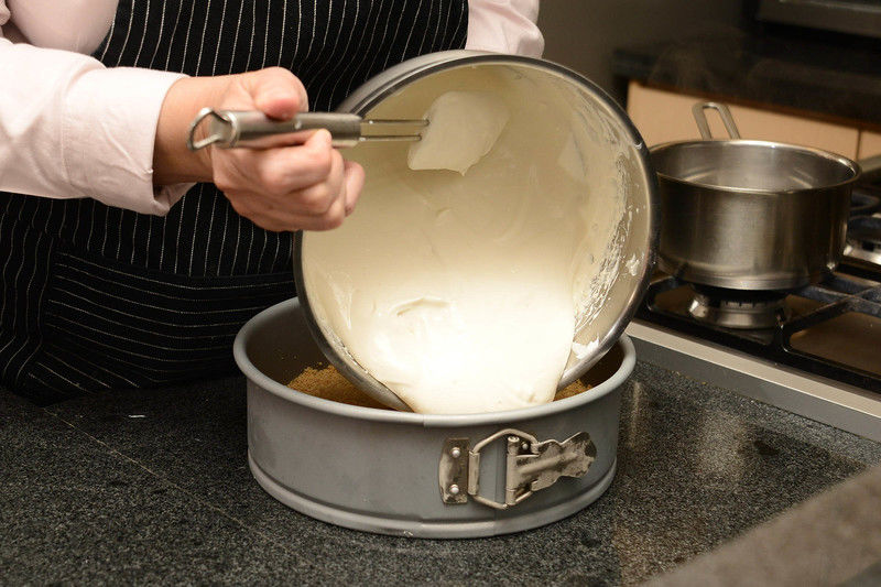 Para preparar la base, colocar las galletas Marías en la licuadora de pocas a la vez y moler hasta que quede polvo. Colocar las galletas molidas sobre el un molde desmoldable para pastel. Añadir la almendra molida y las dos cucharadas de azúcar y mezclar con la mano. Agregar la mantequilla derretida y mezclar bien. Aplanar bien toda la mezcla sobre la base del molde. Una vez compactada, meter al congelador por 10 minutos únicamente.