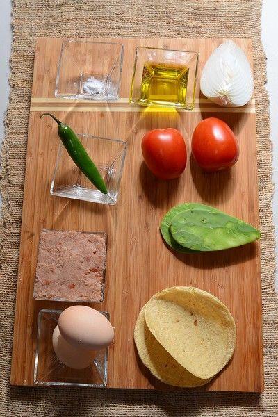 2 piezas de huevo aceite de oliva al gusto 1 pizca de bicarbonato de sodio sal al gusto 1/4 pieza de cebolla blanca 1 pieza de chile serrano 2 piezas de jitomate guaje 2 piezas de penca de nopal 4 piezas de tortilla de maíz