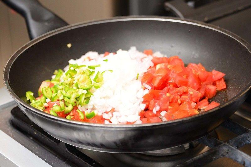 Cortar los nopales en juliana. Cocer en una olla honda mediana con agua y una pizca de bicarbonato durante unos 5 minutos. Escurrir y reservar. Picar el jitomate, el chile y la cebolla. Sofreír en un sartén el jitomate picado, la cebolla y el chile durante 2 minutos.