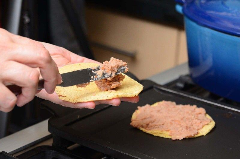 Poner a calentar 2 tortillas sobre el comal e inmediatamente untar una con los frijoles refritos.