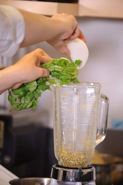 Agregar el trozo de cebolla, el ajo, el cilantro y un poco de sal al moler la última parte de las lentejas.