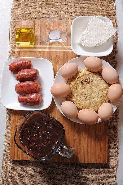 1/2 taza de crema de leche de vaca 2 tazas de frijoles negros cocidos 1/4 cucharita de sal 2 cucharadas de aceite de oliva 200 gramos de queso fresco 200 gramos de chorizo 8 piezas de huevo 12 piezas de tortilla de maíz