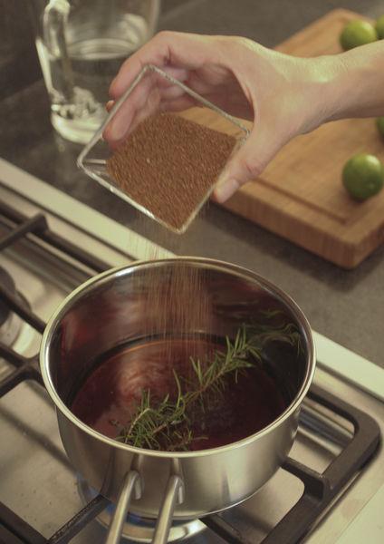 Poner a calentar media taza de agua con el azúcar y la ramita de romero en un sartén, revolver lentamente hasta que se disuelva bien el azúcar.
