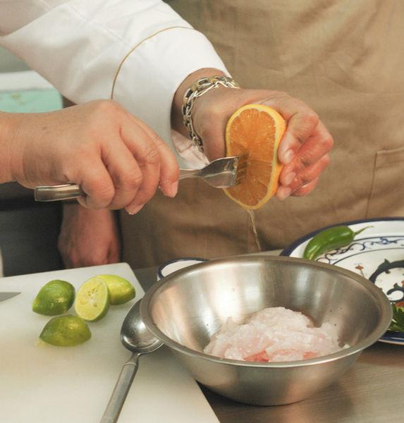 Picar el pescado en trozos pequeños y colocarlo en un tazón. Agregar el jugo de limón, el de naranja y la sal. Dejar reposar en lo que se pican los demás ingredientes.