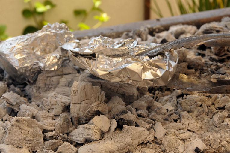 Partir la cebolla en gajos pequeños. En volver 3 o 4 trozos de cebolla en cada pedazo de papel aluminio y colocar directamente sobre las brasas de carbón encendido.