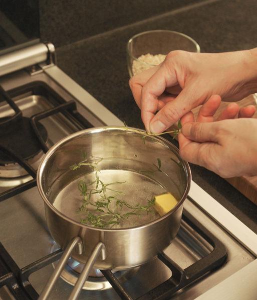 Poner a calentar el agua junto con la cucharada de mantequilla, el romero picado, el tomillo picado y la sal. Dejar hervir unos instantes hasta que se derrita la mantequilla.