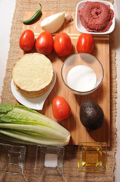 Ingredientes para para el picadillo: 3 cucharadas de aceite de oliva 1/4 pieza de cebolla blanca 8 piezas de tostadas de maíz 1 cucharita de sal 1/4 cucharita de pimienta negra molida 1 diente de ajo 4 piezas de jitomate guaje 1 pieza de chile serrano 250 gramos de carne molida de res Ingredientes para para acompañar: 1 pieza de aguacate 1/2 taza de crema de leche de vaca 1 pieza de jitomate guaje 1 pieza de lechuga