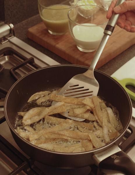 Calentar el aceite de oliva en una sartén abierta. Freír las tortillas cortadas en tiras, volteándolas con frecuencia utilizando una pala con cuidado de que no se rompan. A media cocción sazonar con un poco de sal y continuar hasta que estén doradas crujientes pero no quemadas.