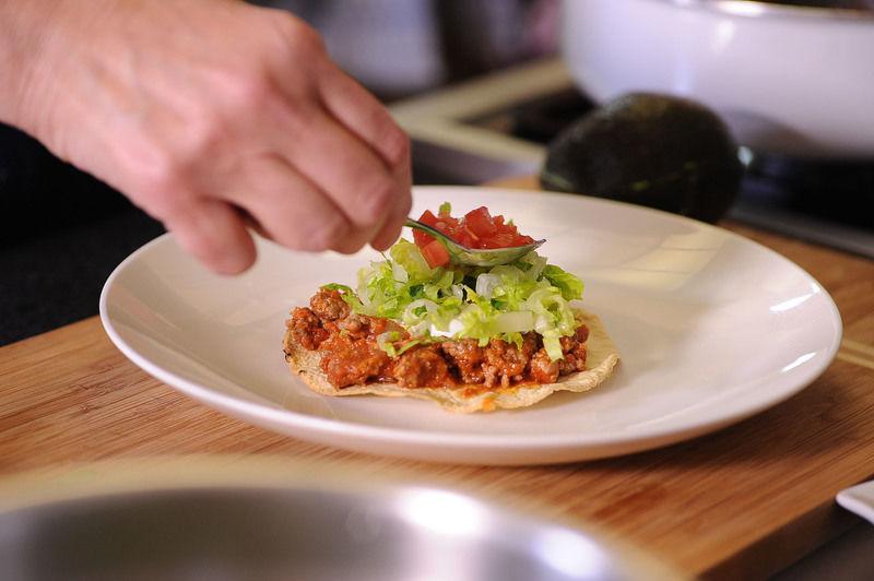 Para servir las tostadas, colocar un poco de picadillo sobre cada tostada, añadir la crema, la lechuga picada y el jitomate picado. Rebanar el aguacate y colocar las rebanadas sobre cada tostada.