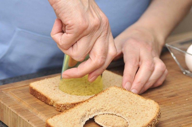 Cortar un círculo en el centro de cada rebanada de pan utilizando un vaso de diámetro pequeño para hacer una especie de marco.