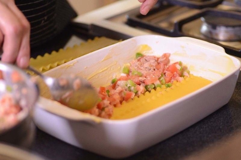 Colocar una capa de lasaña y enseguida una capa de la mezcla de atún y espolvorear un poco de queso.