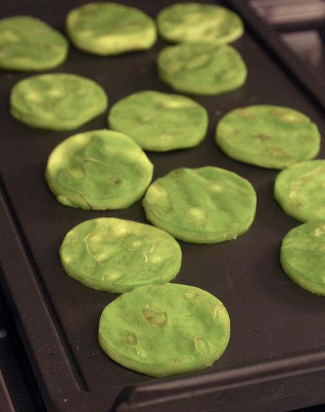 Cortar los nopales en círculos utilizando un cortador de galletas redondo o cuidadosamente con un cuchillo pequeño. Asarlos sobre el comal durante 2 o 3 minutos de cada lado, volteándolos con una pala.