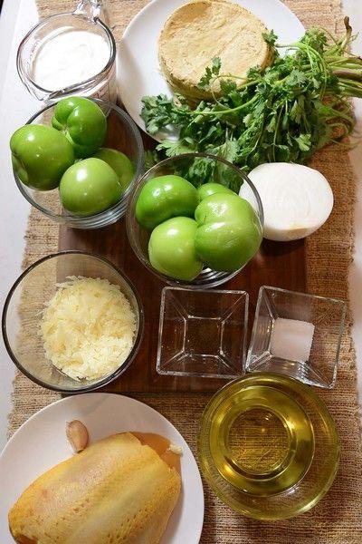 1 cucharita de sal 1/4 cucharita de pimienta negra molida 1 taza de aceite de canola 1/2 taza de queso manchego 1 taza de crema de leche de vaca 1/2 manojo de cilantro 1 diente de ajo 1/2 pieza de cebolla blanca 10 piezas de tomate verde (tomatillo) 1 pieza de pechuga de pollo 12 piezas de tortillas de maíz