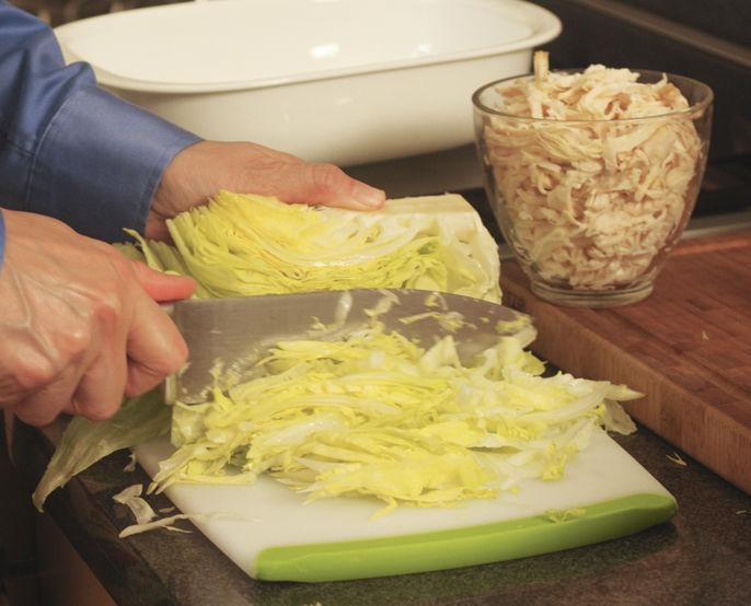 Desmenuzar la pechuga de pollo cocida. Picar la lechuga en tiras delgadas, cortar la cebolla en rodajas finas, el pepino en cubos pequeños y el chile finamente.