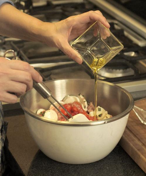 Cortar en rebanadas delgadas el queso. Picar el jitomate y hojas de albahaca. Colocar en un tazón el queso con el jitomate, el atún y la albahaca. Agregar aceite de oliva, sazonar con sal y pimienta. Revolver con una cuchara de madera.