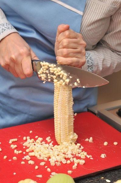 Desgranar los elotes con un cuchillo sobre la tabla para picar, cortando sólo dos filas a la vez. Una vez que se desgranó todo, repasar con el cuchillo para sacar toda la pulpa.